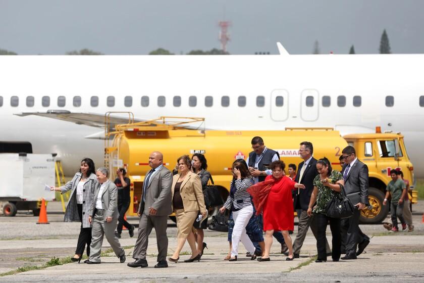 Una comitiva del Servicio de Inmigración y Control de Aduanas de Estados Unidos observa a varios deportados bajar de un avión proveniente de Meza, Arizona (EEUU).