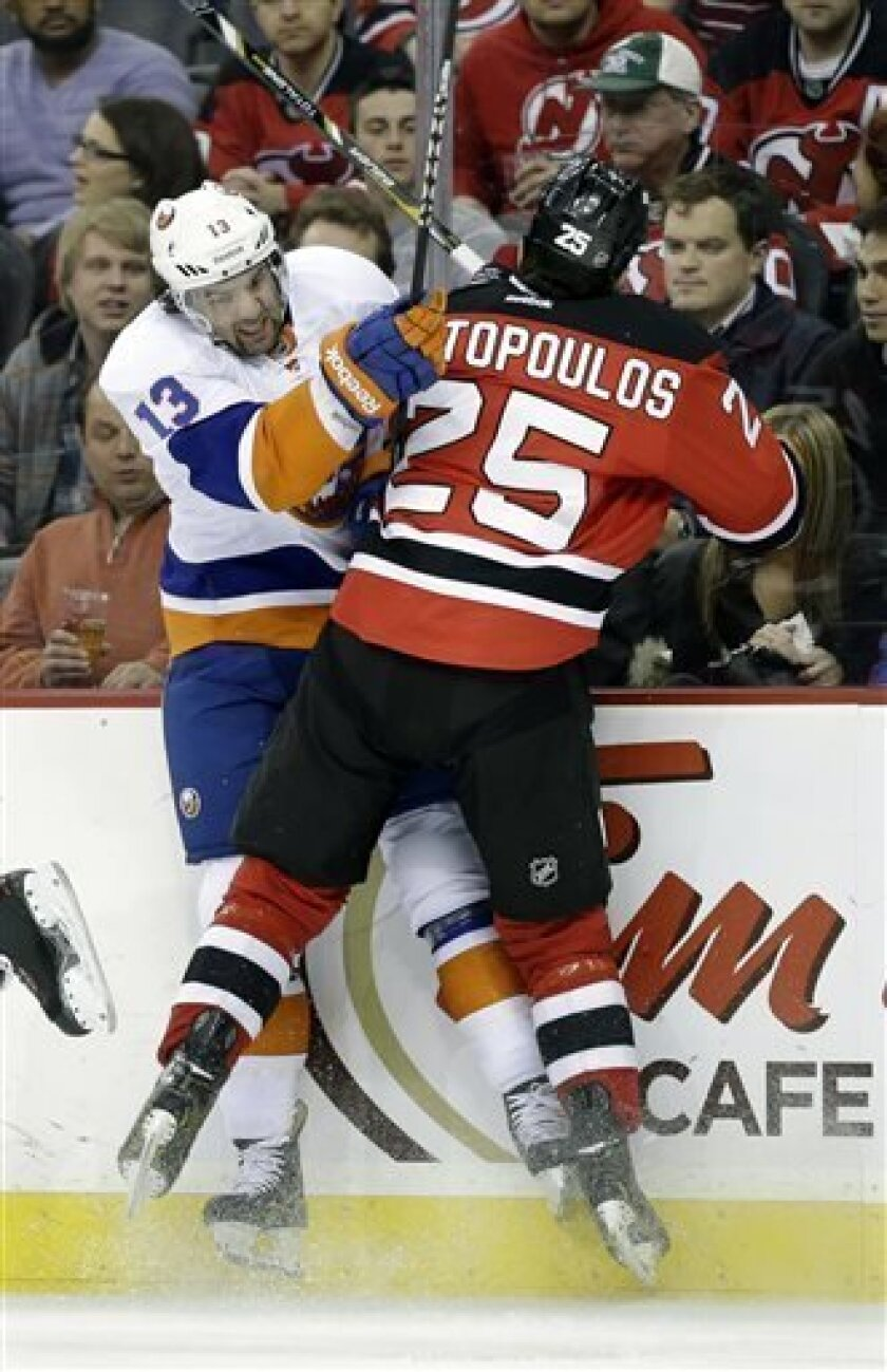 New York Islanders' Colin McDonald (13) collides with New Jersey Devils Tom Kostopoulos (25) during the first period of an NHL hockey game Monday, April 1, 2013, in Newark, N.J. (AP Photo/Mel Evans)