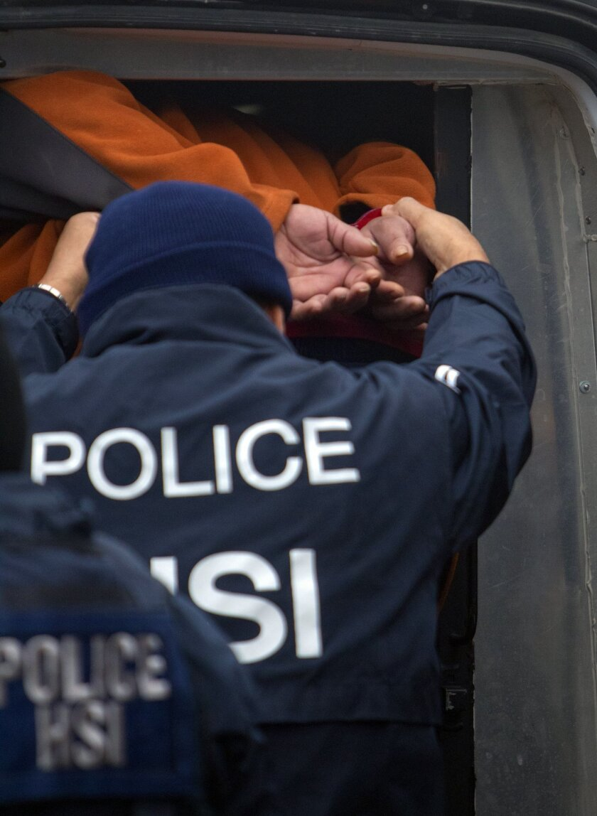 A federal agent helps a person into a vehicle after raiding a business, Thursday, Jan. 30, 2014, in southwest Houston. The raid was part of a crackdown on an alleged human smuggling ring operating in Texas and other states. (AP Photo/Houston Chronicle, Cody Duty) MANDATORY CREDIT.