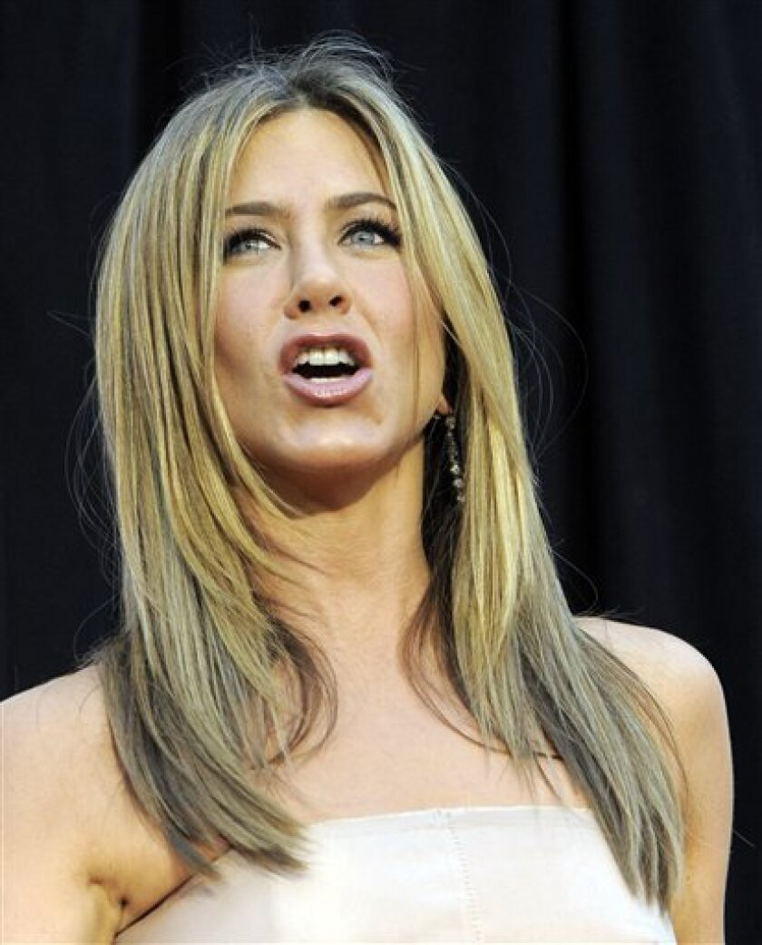 """Jennifer Aniston, a cast member in """"The Switch,"""" reacts to photographers at the premiere of the film in Los Angeles, Monday, Aug. 16, 2010. (AP Photo/Chris Pizzello)"""