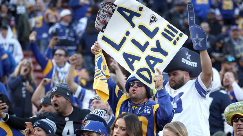 Rams fans cheer among Cowboys fans during the Rams' Divisional Round victory over Dallas at the Coliseum on Jan. 12.