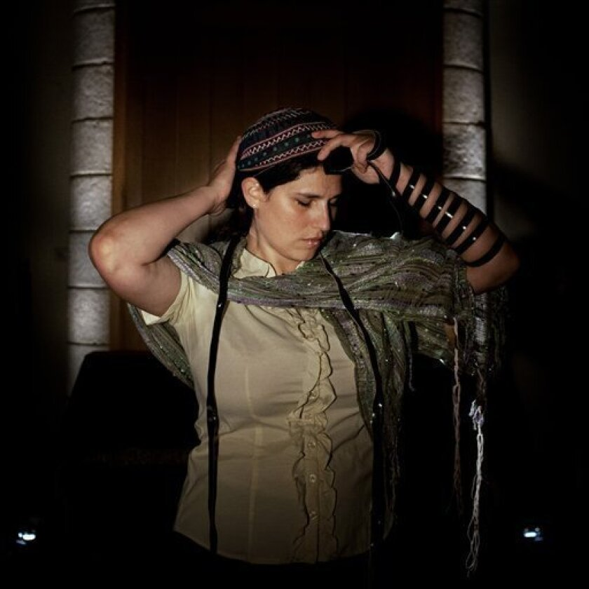 In this photo taken Wednesday, June 19, 2013, Israeli Rabbi of the Ramot Zion community, Chaya Baker poses for a photo as she puts on Tefilin also known as Phylacteries at a Synagogue in Jerusalem. Depending on whom you ask, these women are either pioneers or provocateurs. They are part of the libe