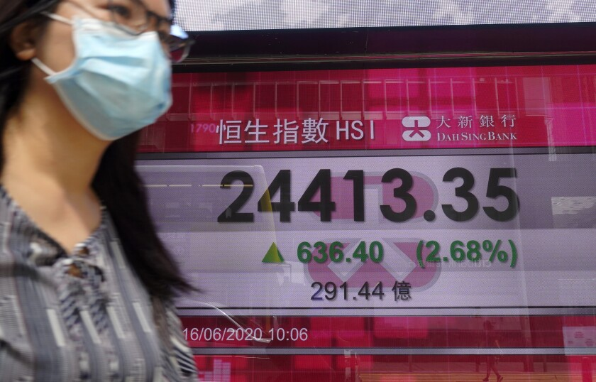 A woman wearing a face mask walks past a bank electronic board showing the Hong Kong share index at Hong Kong Stock Exchange Tuesday, June 16, 2020. Asian shares rose Tuesday, cheered by fresh moves by the U.S. Federal Reserve to support markets battered by the coronavirus pandemic. (AP Photo/Vincent Yu)