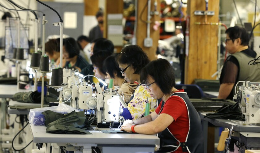 A group of workers at C.C. Filson Co. work at their sewing machines in Seattle on Aug. 31.