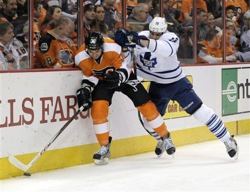 Toronto Maple Leafs' Mike Brown, right, checks Philadelphia Flyers' Ruslan Fedotenko, of Ukraine, in the first period of an NHL hockey game, Monday, Feb 25, 2013, in Philadelphia. (AP Photo/Michael Perez)