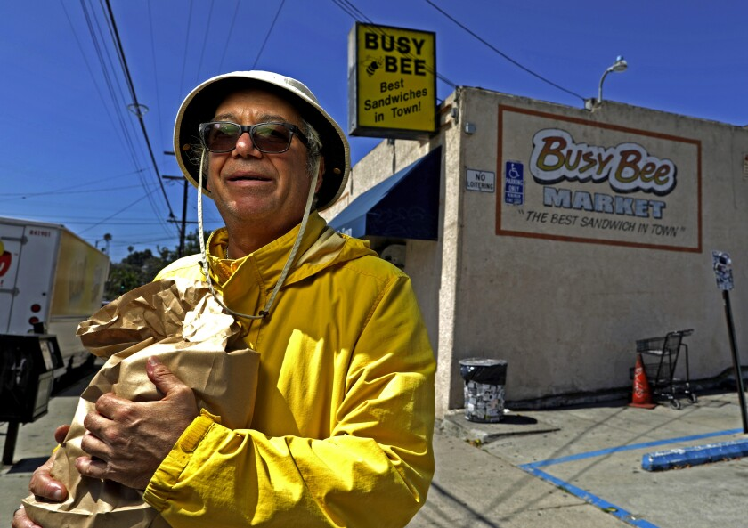 Bassist Mike Watt with a bag of sandwiches outside Busy Bee Market in San Pedro