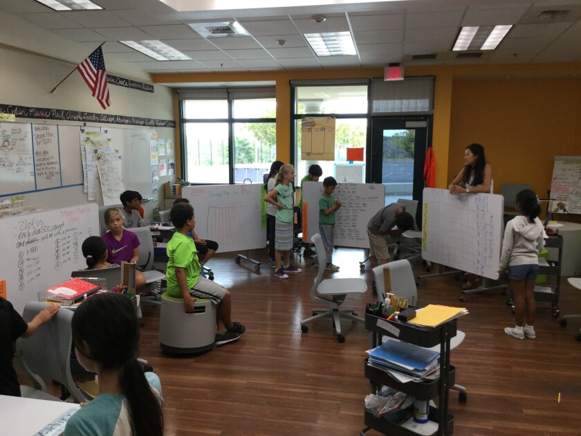 Students in one of DMUSD modern learning studios use tables that they can write on and then flip-up to share their work with the class.