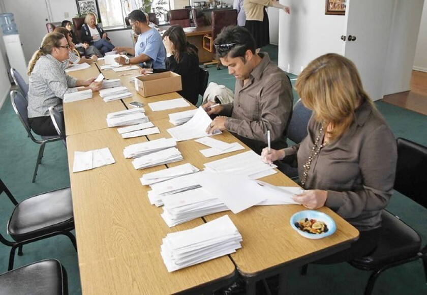 Members of the Newport-Mesa Federation of Teachers organize union ballots in their Costa Mesa office on Thursday. The ballots overwhelming approved a no-confidence vote in Supt. Jeffrey Hubbard, who is accused of three felonies related to his previous job in Beverly Hills.