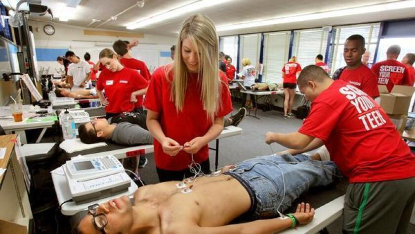 Fifteen-year-old track athlete D'Isaac Young, of San Diego, gets connected to an EKG machine for his heart screening by volunteers Amelia Schricker, left, and Jared Ekong, at right, at Madison High School last year.