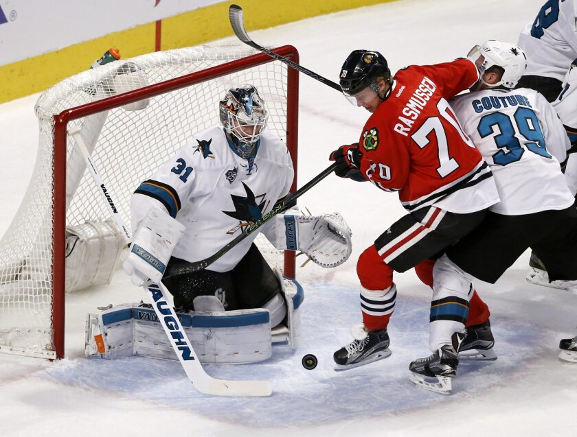 Chicago Blackhawks left wing Dennis Rasmussen (70) is unable to get a shot on San Jose Sharks goalie Martin Jones (31) as Logan Couture also defends during the first period of an NHL hockey game Tuesday, Feb. 9, 2016, in Chicago. (AP Photo/Charles Rex Arbogast)