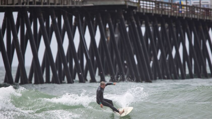 A surfer rides a wave in front of the Imperial Beach Pier on Thursday, May 17th, 2018.