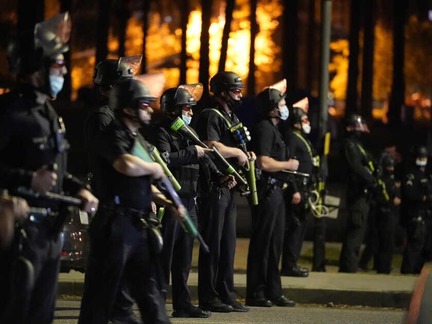 Los Angeles police officers move in to arrest demonstrators in the Echo Park Lake homeless encampment in Los Angeles.