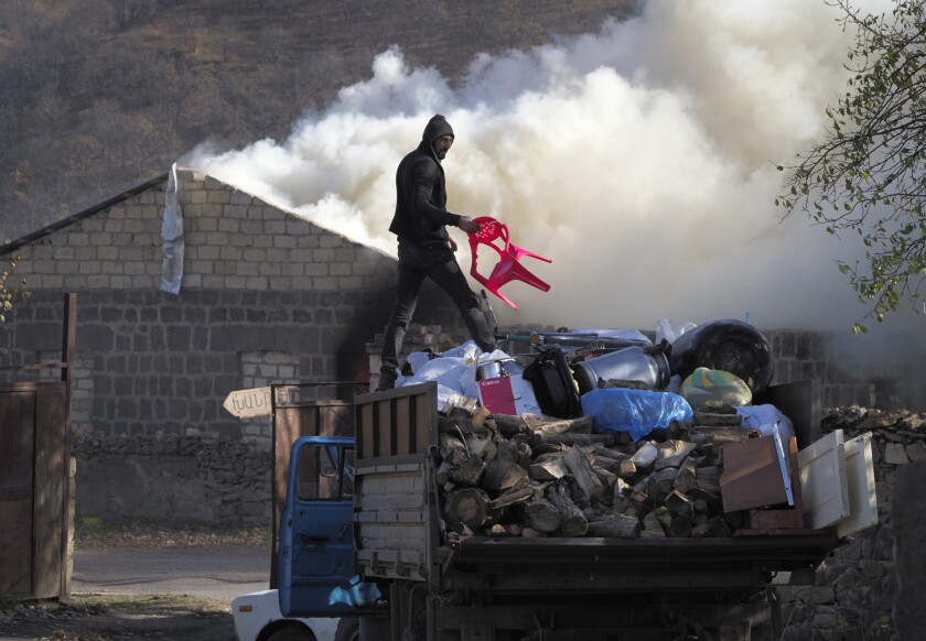 A man loads possessions on his truck after setting his home on fire on Friday in the separatist region of Nagorno-Karabakh.