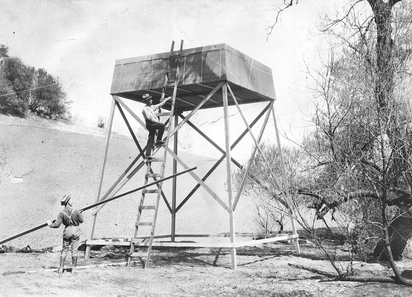 "Charles Hatfield (on the ladder) and his younger brother with one of their rain towers, in Coalinga, Calif. The pair built a similar 20-foot tower in the woods east of San Diego and began what one city official would later call ""an incantation aimed at wringing moisture from the air."" What followed was a destructive downpour."
