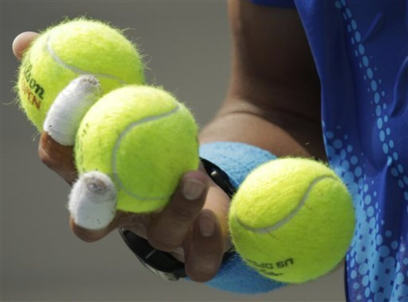 Rafael Nadal of Spain selects a ball to serve to David Nalbandian of Argentina during the U.S. Open tennis tournament in New York, Sunday, Sept. 4, 2011. (AP Photo/Charlie Riedel)