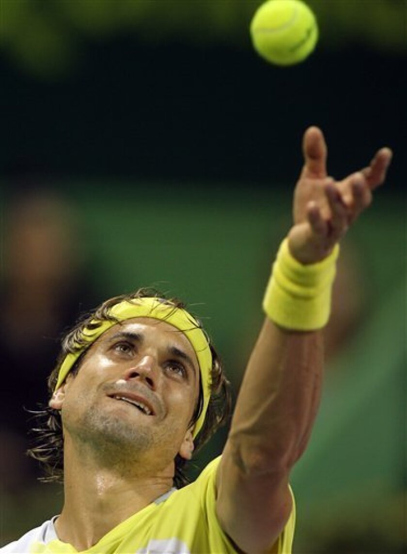 Spain's David Ferrer serves the ball to Germany's Dustin Brown during the Qatar ATP Open Tennis tournament in Doha, Qatar, Tuesday, Jan. 1, 2013. (AP Photo/Osama Faisal)
