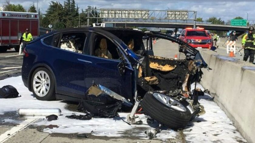 Emergency personnel work the scene of a fatal Tesla SUV crash in Mountain View, Calif. Tesla says the vehicle was operating on Autopilot.