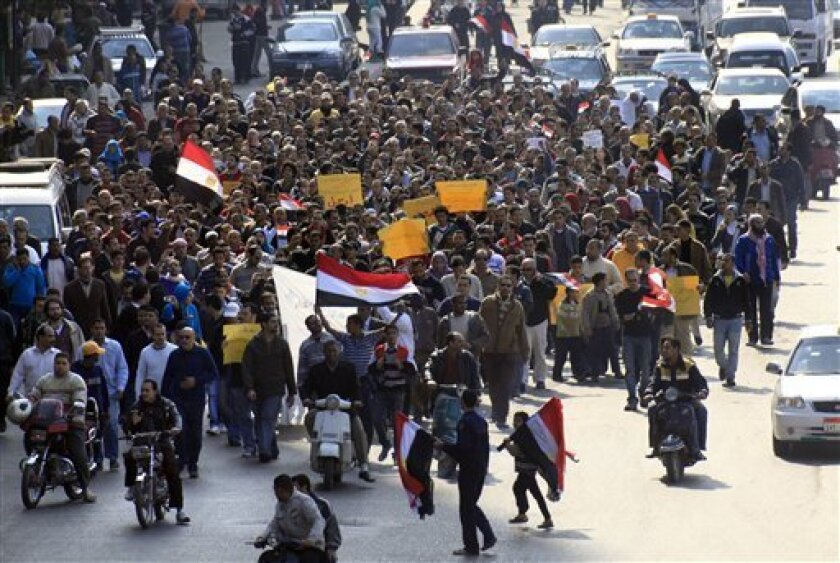 Anti-government protesters march through a street in Cairo, Egypt, Friday, Feb. 11, 2011. Egypt's military threw its weight Friday behind President Hosni Mubarak's plan to stay in office through September elections while protesters fanned out to the presidential palace in Cairo and other key symbol