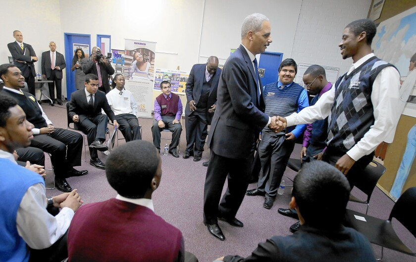 Atty. Gen. Eric H. Holder Jr. shakes hands with an an attendee at the Crenshaw event, held as part of his Smart on Crime initiative, aimed at making the criminal justice system fairer and more efficient.