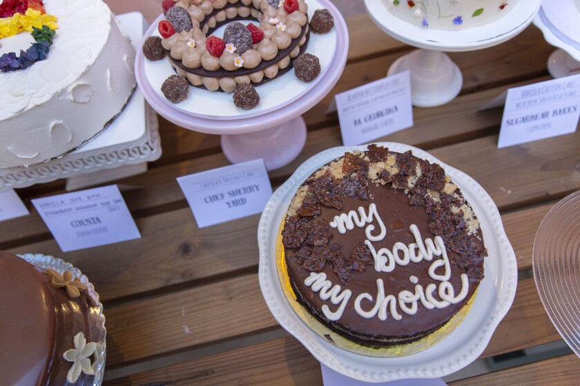 "A cake iced with the words ""my body my choice"" and other desserts made for the Gather for Good bake sale"