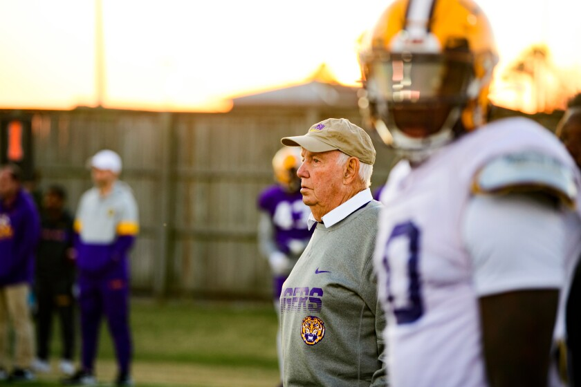 Former USC football coach John Robinson stands on the sideline during a practice at Louisiana State.