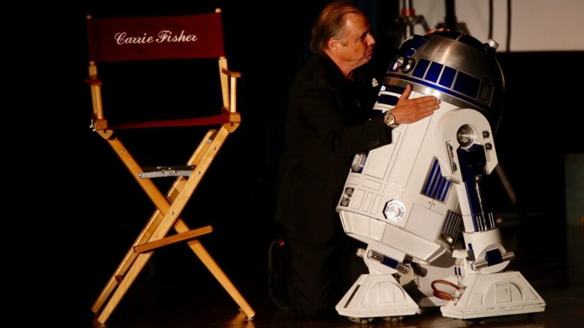 Todd Fisher hugs R2-D2 at a memorial for his sister, Carrie Fisher, and his mother, Debbie Reynolds, at Forest Lawn Memorial Park-Hollywood Hills in Los Angeles on Saturday. (Francine Orr / Los Angeles Times)
