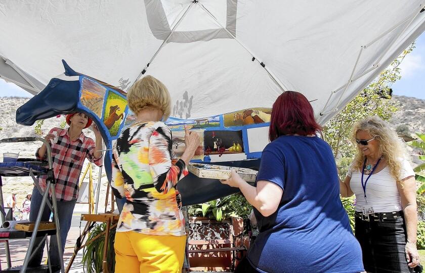 From left, Natalia Eremeyeva-Duarte, Sandy Clark, Carol Heiman-Greene and Nina K paint a fiberglass horse sculpture at the Art-A-Fair grounds on Aug. 13.