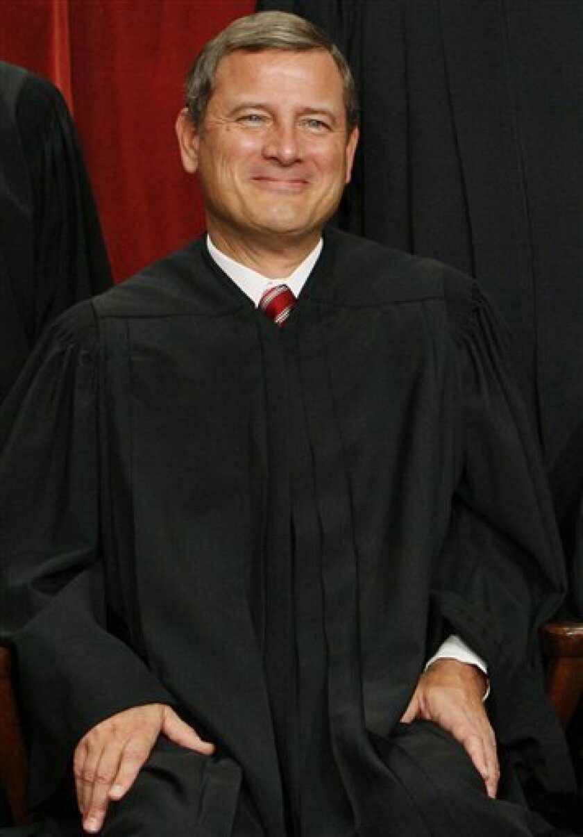 Chief Justice John Roberts sits for a new group photograph with other Supreme Court judges, Tuesday, Sept. 29, 2009, at the Supreme Court in Washington. (AP Photo/Charles Dharapak)