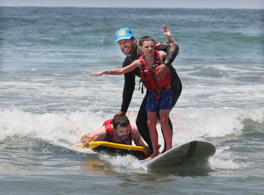 Adam Paskowitz surfs with Aiden Cullen-Moore, 7, right, while grabbing on to Jeremy Sicile-Kira, 27, who surfed up to them on his boogie board during Wednesday's Surfers Healing camp at Tourmaline Beach.