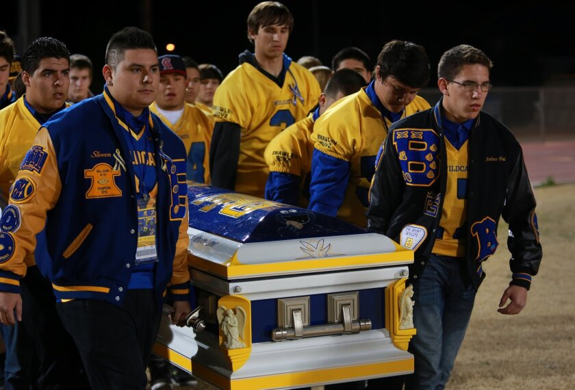 Steven Acosta, left, and Josh Godinez led other football players carrying the casket of slain teammate Martin Garza to the 50-yard line at his memorial service, a three-hour remembrance by Garza's coaches, teachers and classmates. The nearly 2,000 in attendance lined up in the chilly night to view Garza in his open casket at Warne Field, where he was a left guard and a leader.