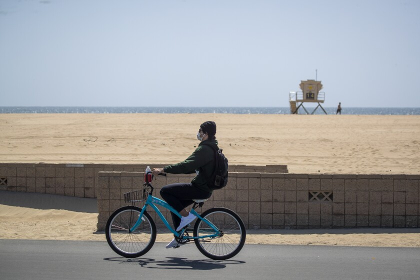 A man wears a protective mask while biking on the mostly empty boardwalk in Huntington Beach on Thursday.