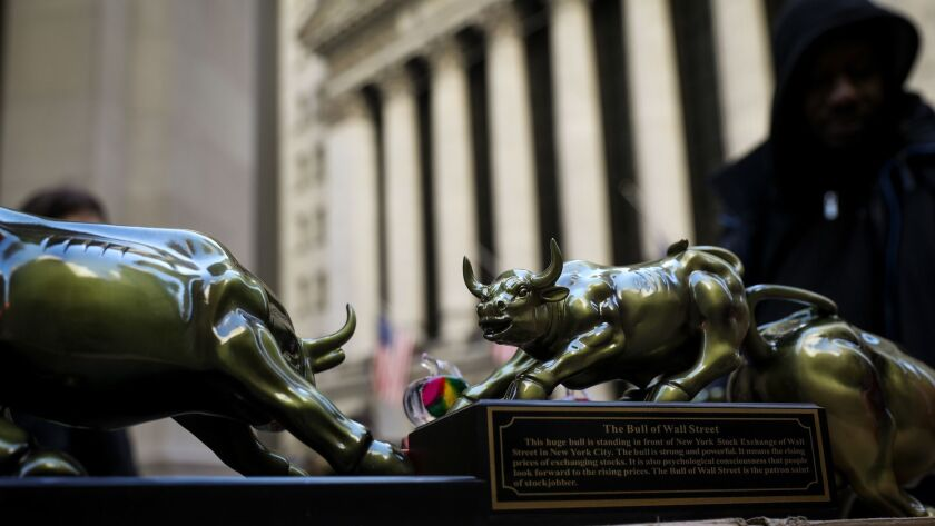 A street vendor sells replicas of the Wall Street Bull statue outside the New York Stock Exchange on March 26.