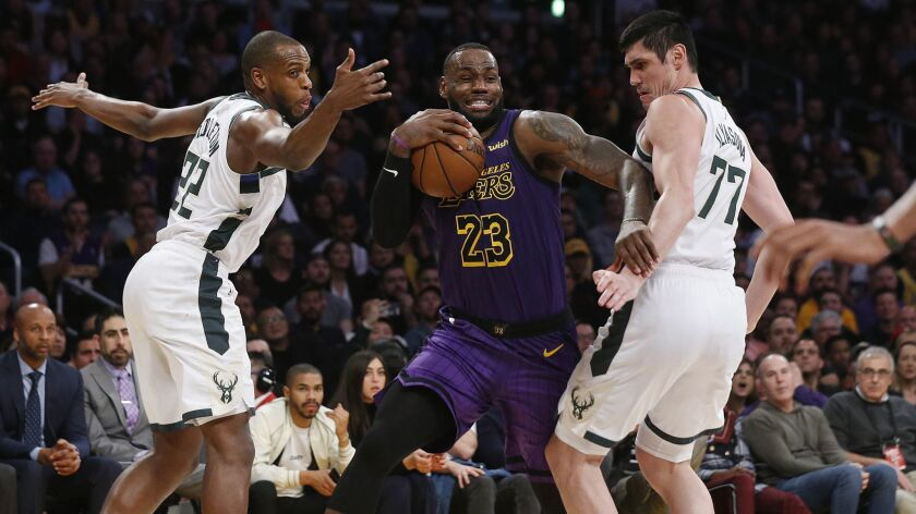 Lakers' LeBron James (23) is guarded by Milwaukee Bucks' Khris Middleton (22) and Ersan Ilyasova (77) in the second half.