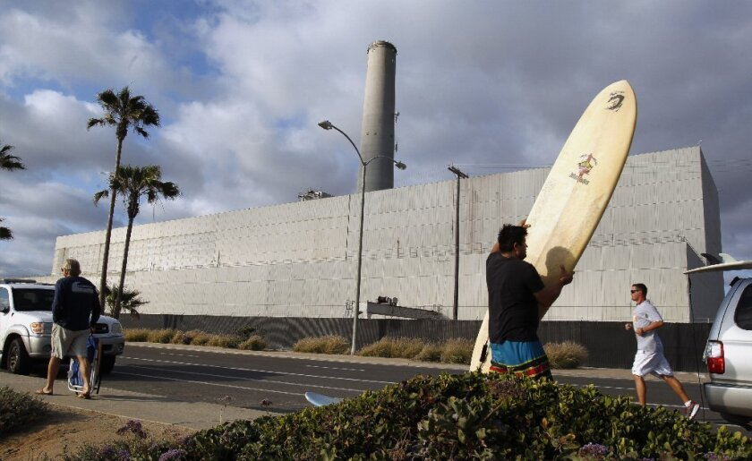 CARLSBAD , May 23, 2016 | With the Encina Power Station in the background, Jose Rolon loads up his surfboard after he and his family spent an afternoon on the beach in Carlsbad on Monday. | Photo by Hayne Palmour IV/San Diego Union-Tribune