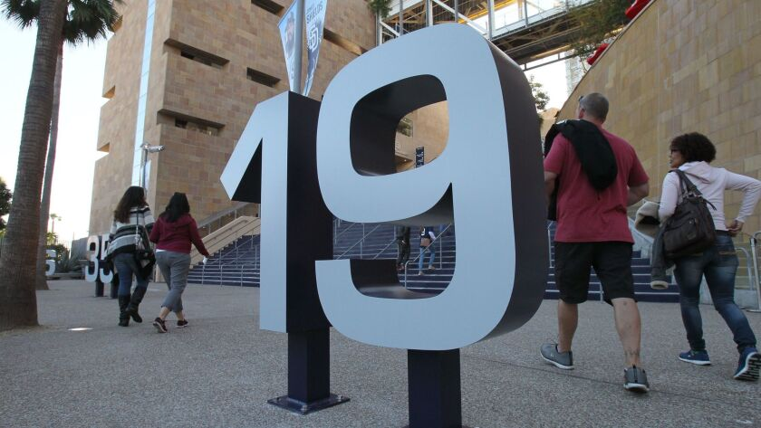 At the 6 pm opening of the gates for the Padres/White Sox exhibition game fans pass a steel sculpture of Tony Gwynn's number.