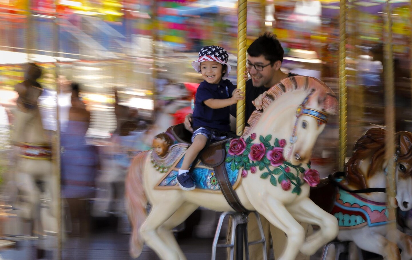 Two-year-old Leo Vannostrand, left, gets a ride on the carousel with his dad, John Vannostrand, right, on the final day of the 2018 San Diego County Fair.