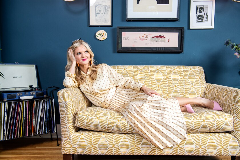 Arden Myrin reclines on a sofa in her home in Silver Lake.