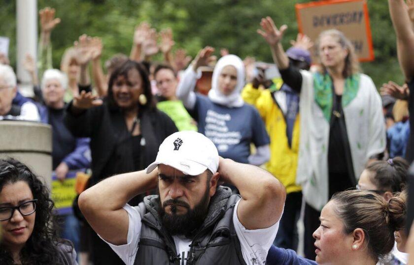 José Robles se lleva las manos a la nuca mientras simpatizantes extienden sus brazos en un tipo de bendición antes de que se presente ante autoridades del Servicio de Control de Inmigración y Aduanas en Tukwila, Washington, que lo arrestaron.
