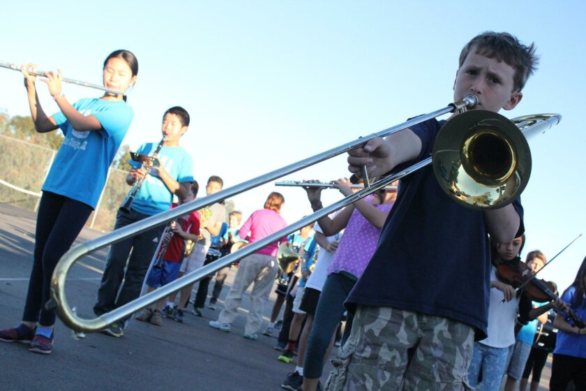 Mission Bay Montessori Academy band members have been practicing an extra 12 hours a week for their La Jolla Christmas Parade performance. Andrew Hilgers (pictured at right), 9, masters his trombone playing, while 11-year-old Katherine Huang (at left) plays the flute and Eric Lin (second from left)