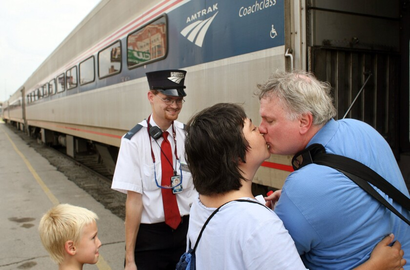 Brandon Bostian, then an assistant conductor. stands by on Aug. 21, 2007, as Sandra Palmer says goodbye to her boyfriend, Clyde Simpson, as he leaves for work in Chicago at the Amtrak station in St. Louis. Bostian was the engineer of the Amtrak train that derailed in Philadelphia.