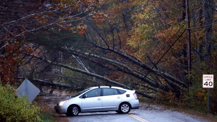 A motorist turns around after finding downed trees blocking a road in Freeport, Maine, on Monday. A strong wind storm has caused widespread power outages.
