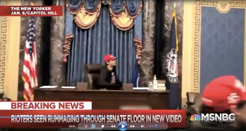 A man was captured on video camera inside the Senate chambers sitting at the Presiding Officer's chair