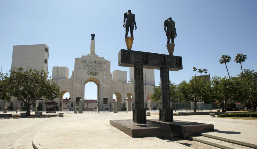 The Los Angeles Memorial Coliseum with a pair of athlete statues installed for the 1984 Summer Olympics, foreground.