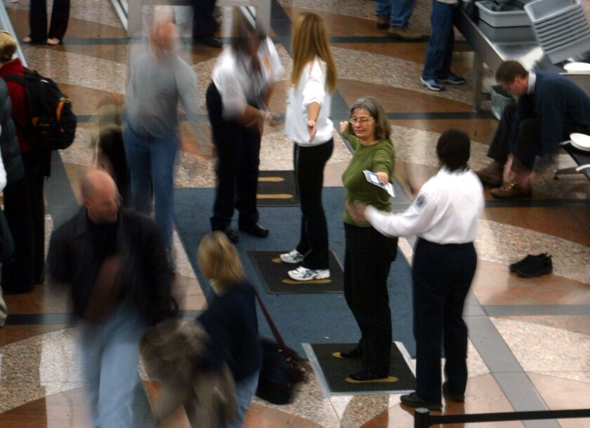 Transportation Security Administration agents screen travelers at Denver International Airport in 2003.