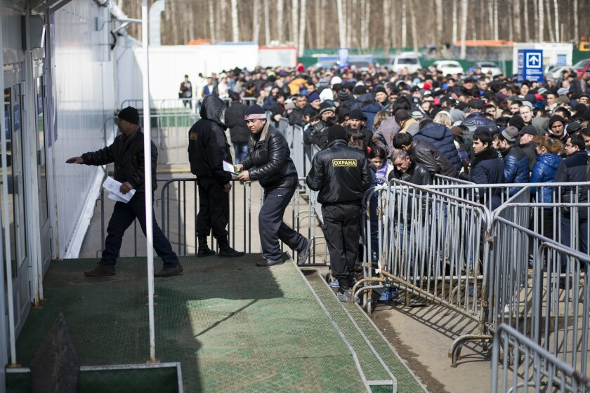 In this photo taken on Wednesday, April  22, 2015, Migrants enter a tent as others stand in line to register at Moscow's migration center in Sakharovo, a village about 60 kilometers (35 miles) south of Moscow, Russia. Moscow's migration center works 24 hours a day, seven days a week to process work