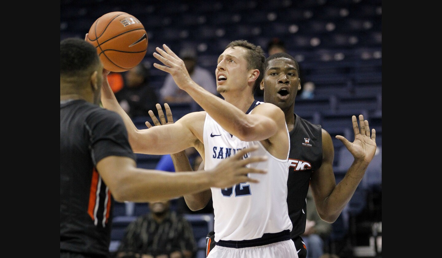 USD's Brett Bailey tries to shoot while in between the Pacific Tigers' T.J. Wallace, left, and Anthony Townes during the first half.