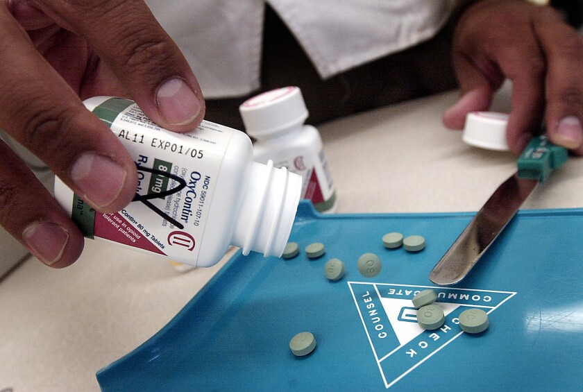 A pharmacist displays tablets of the prescription painkiller OxyContin. A new study finds that 91% of people who had a nonfatal overdose of opioid painkillers like OxyContin continue to get refills from a doctor.
