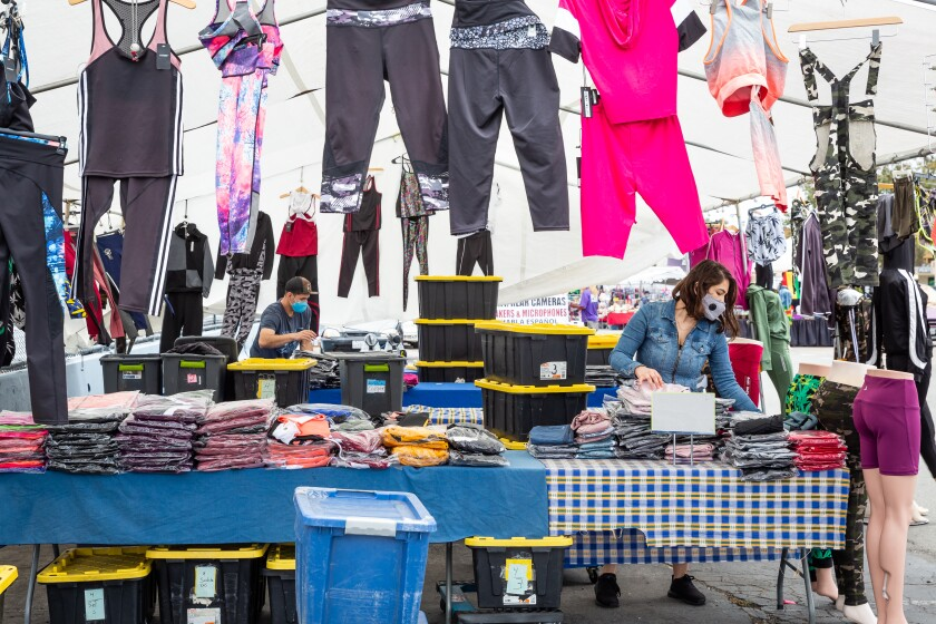 Alfonso Lopez and Iram Moran fold clothes at Nana Sport at Kobey's Swap Meet.