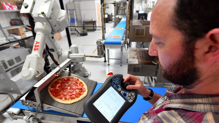 Josh Goldberg controls a robot whose sole purpose is to take a pizza off the conveyor belt and put i