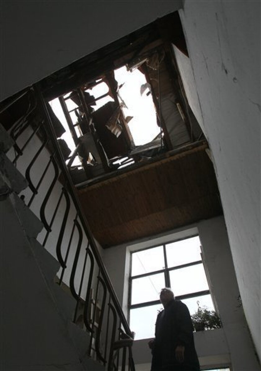 A man checks out his damaged apartment building in Kraljevo, about 130 kilometers south of Belgrade, which was damaged in the earthquake early Wednesday, Nov. 3, 2010. The 5.3 magnitude earthquake hit central Serbia early Wednesday killing a few people and injuring dozens. (AP Photo/Darko Vojinovic)